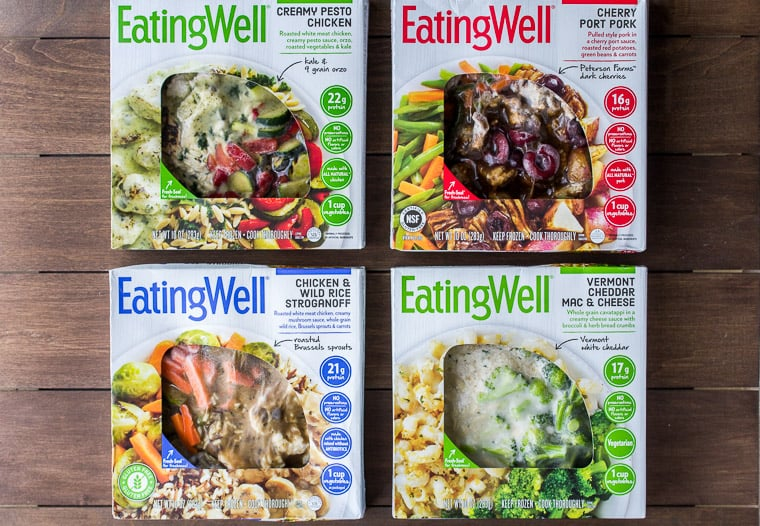 4 EatingWell Frozen Meals on a Wood Back Drop