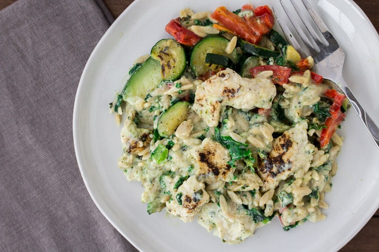 EatingWell Creamy Pesto Chicken on a White Plate with a Gray Napkin