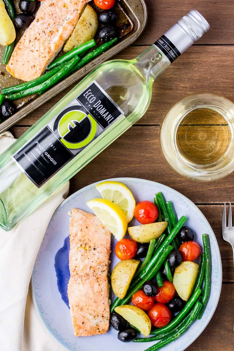 Baked Salmon and Vegetables on a Blue Plate with a Bottle of Wine, Glass of Wine, and the Sheet Pan in the Background