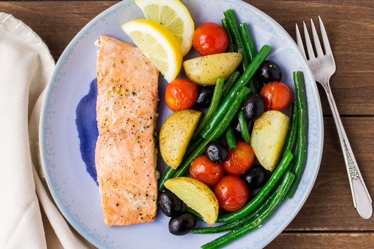 Baked Salmon and Vegetables on a Blue Plate with a Beige Napkin and Fork
