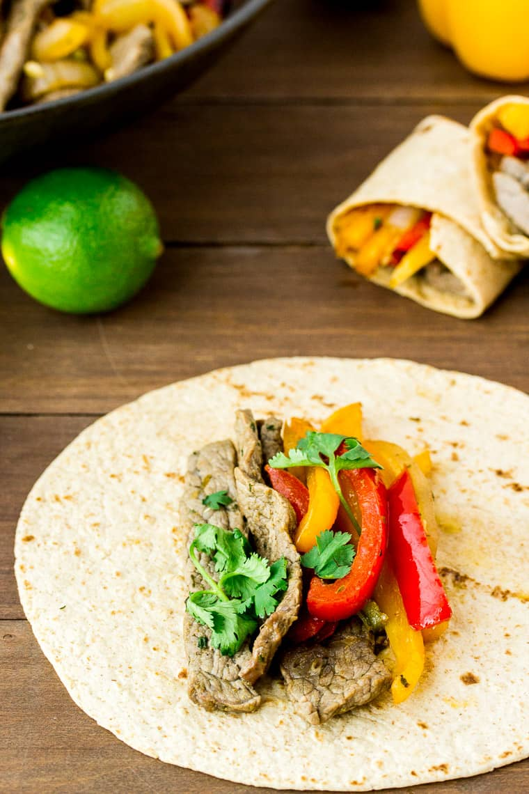 Low Carb Steak Fajita Wraps on a Wood Back Drop with a Lime, Peppers, and Skillet