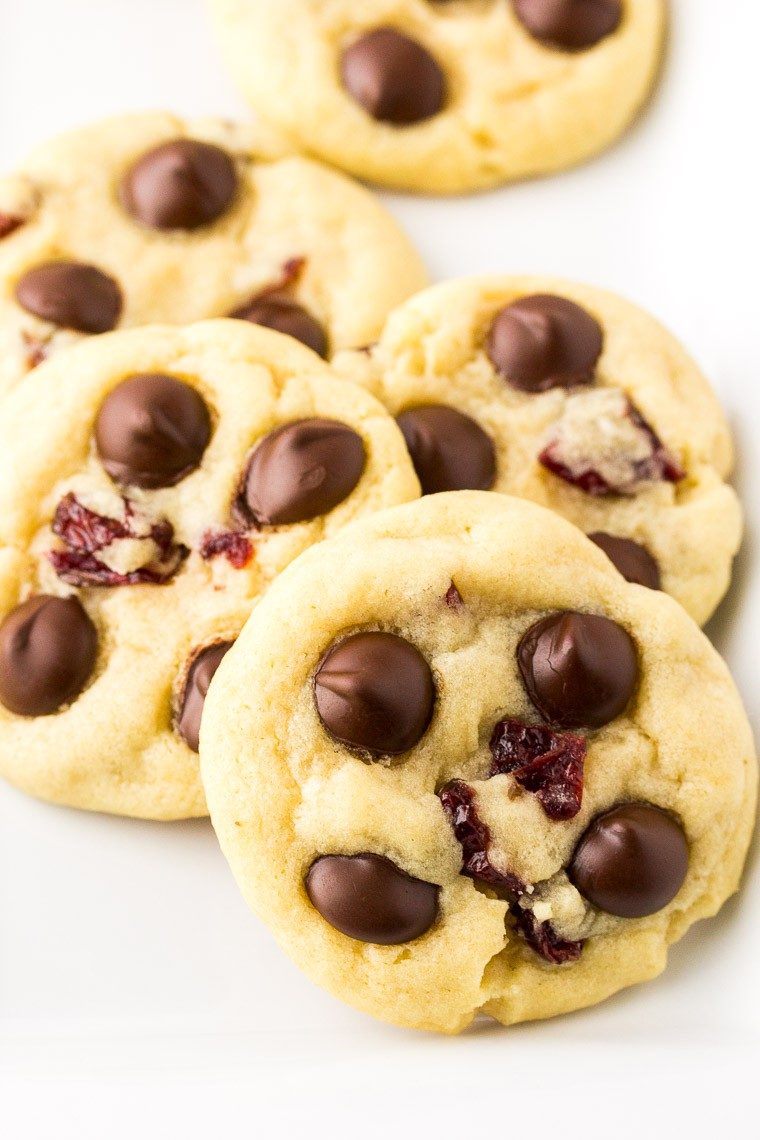 Dark Chocolate Chip Cranberry Cookies stacked on a white background