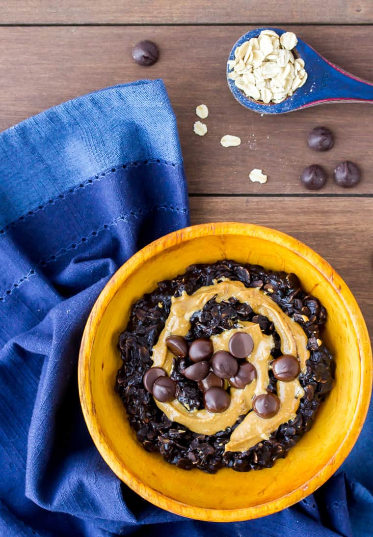 Dark Chocolate Peanut Butter Oatmeal in an Orange Wood Bowl with a Blue Napkin