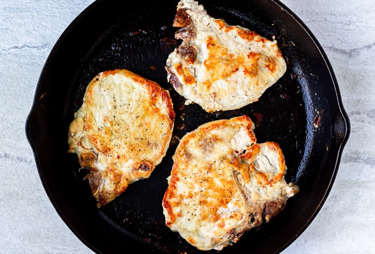 2 pork chops seared in a cast iron skillet over a white background