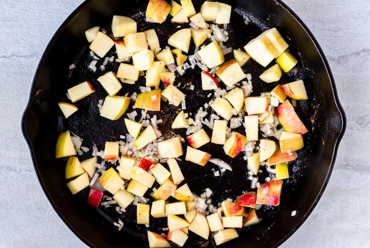 Apples and shallot cooking in a cast iron skillet over a white background