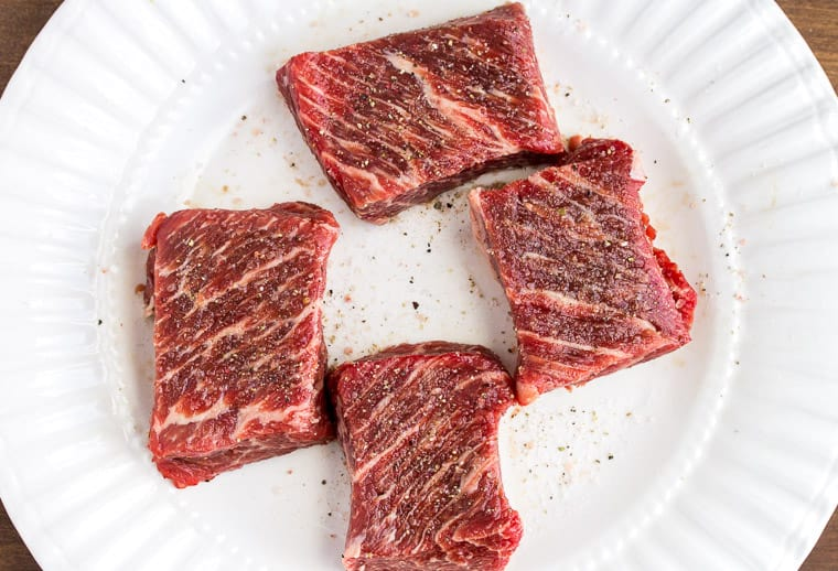 Boneless Short Ribs Seasoned with Salt and Pepper on a White Plate