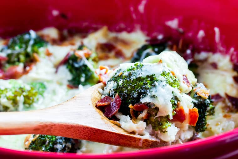 A close up of a wooden spoon filled with broccoli, bacon, cheese and chicken being lifted out of a red casserole dish