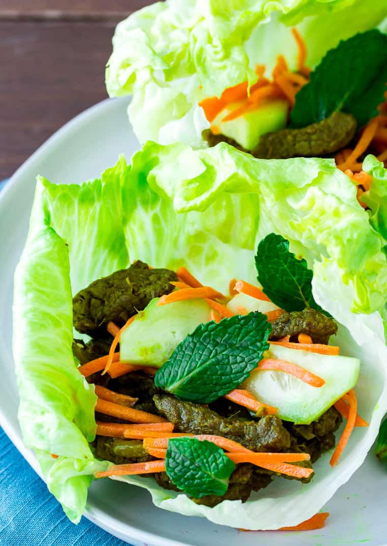 Lemongrass-steak Lettuce Cups with Pickled Vegetables on a White Plate with a Teal Napkin