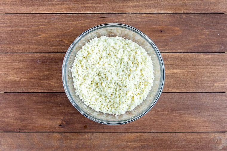 A small glass bowl of riced cauliflower on a wood background