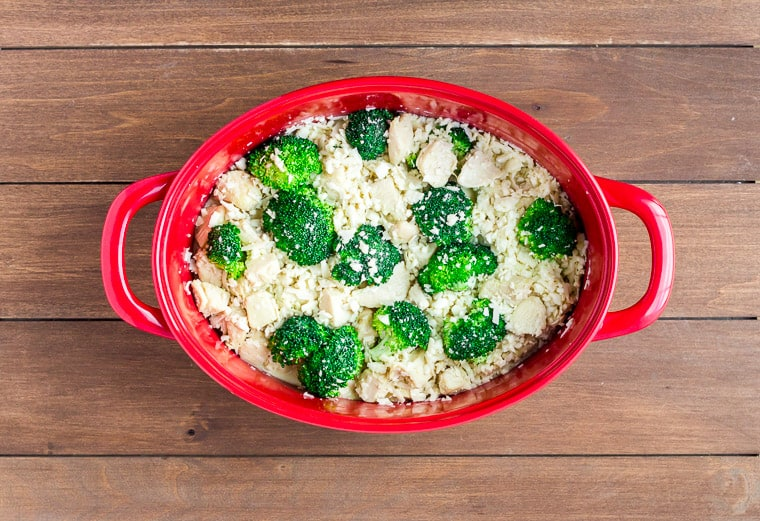 Unbaked Cheesy Chicken Casserole in a Red Casserole Dish on a wood background