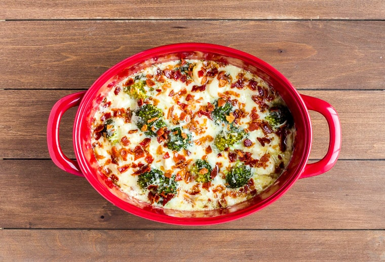 Baked Cheesy Chicken Casserole in a Red Casserole Dish on a wood background