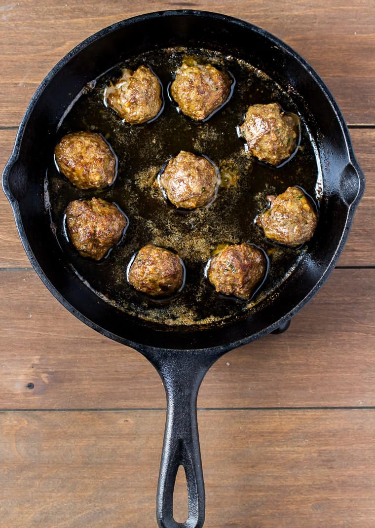 9 Meatballs Frying in a Cast Iron Skillet on a wood background