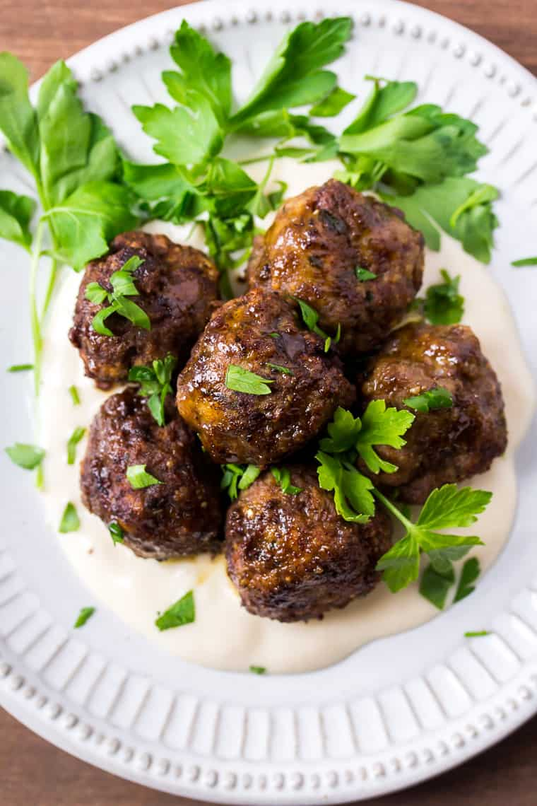 Close up of 5 Italian Meatballs on a White Plate with Parsley on a Wood Backdrop