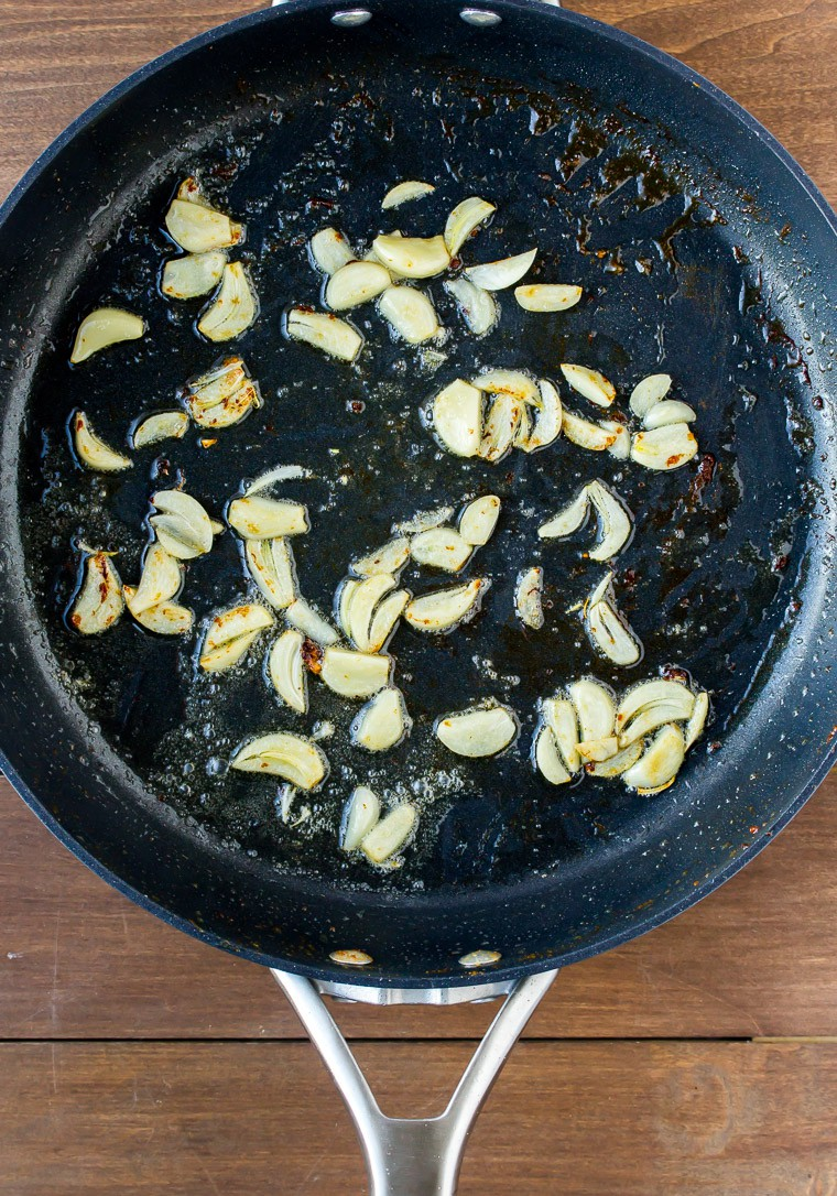 Sliced Garlic Cooking in Butter in a Black Skillet on a Wood Background