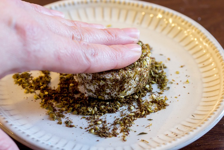 Close up of fingers pressing a round of goat cheese into za'atar spices on a white plate