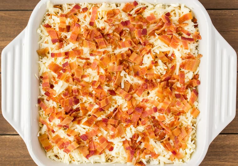 Close up overhead view of the Keto Breakfast Casserole prepared and ready to bake topped with bacon and more cheese in a white casserole dish on a wood background