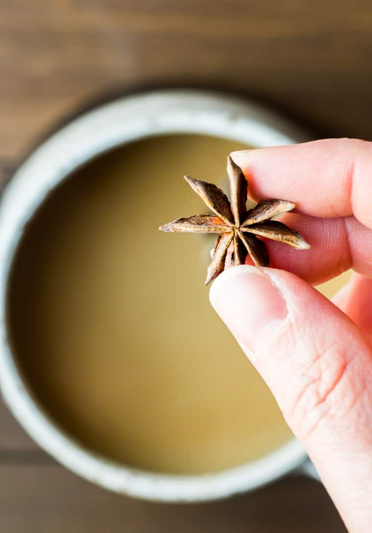 Holding a Piece of Star Anise Over the Mug of Chai Tea Latte