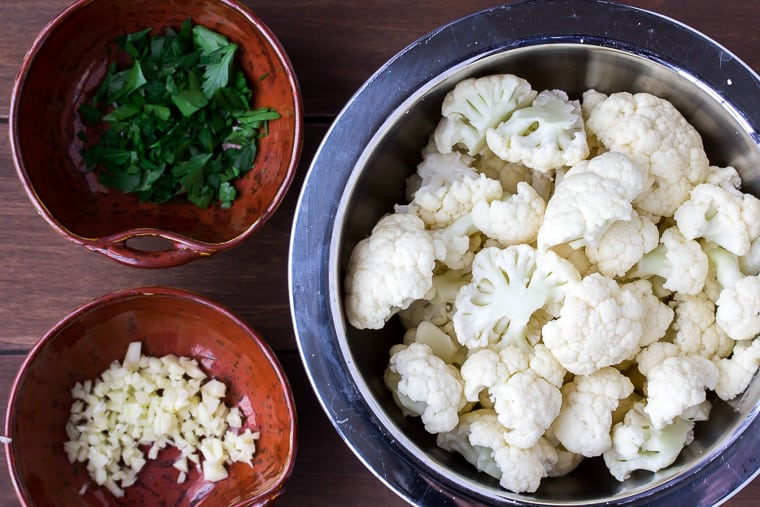 Cauliflower florets in a silver bowl and parsley and garlic in 2 small brown bowls on a wood background
