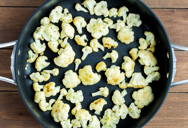 Browned cauliflower in a black skillet over a wood background