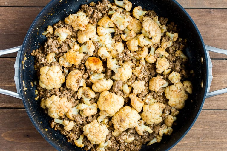 ground Beef and Cauliflower in a black skillet with a light sauce over a wood background