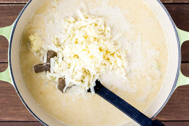 Shredded cheddar cheese on top of a creamy soup in a pot before being stirred in with a black spoon over a wood background