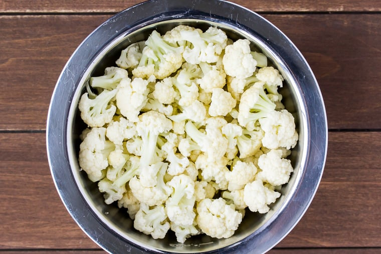 Overhead view of cauliflower florets in a silver bowl over a wood background