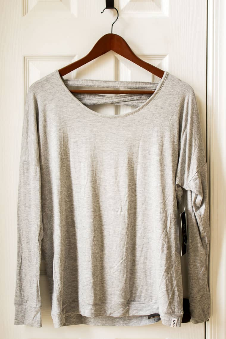 Stitch Fix Andrew Marc Performance Annwin Cut Out Knit Top on a wood hanger in front of a white door
