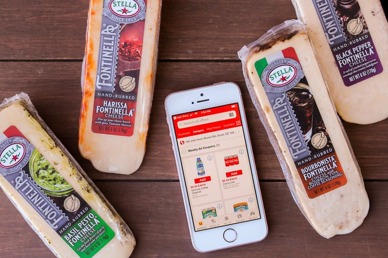 Phone showing safeway mobile app with 4 blocks of cheese on a wood backdrop