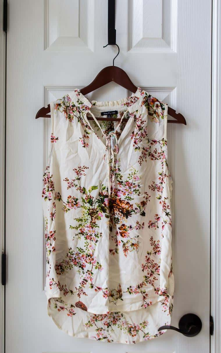 Stitch Fix Pink Clover Mahalo Tie Neck Top in cream with a floral design on a hanger over a white door
