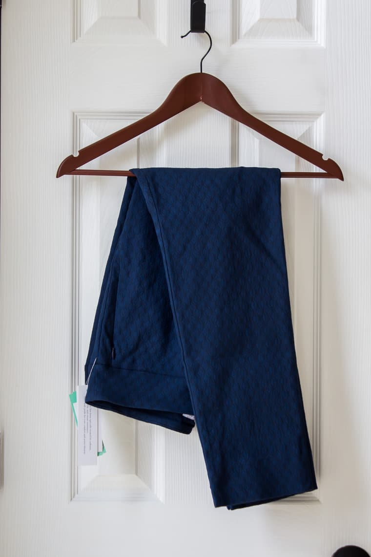 Margaret M Sylvie Printed Straight Leg Pant in dark blue on a hanger over a white door