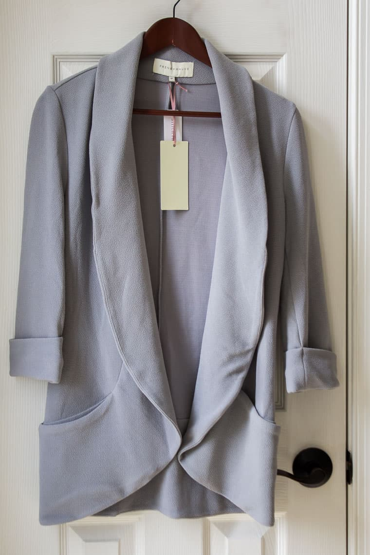 French Mauve Melanie Knit Tunic Blazer in light gray on a hanger over a white door