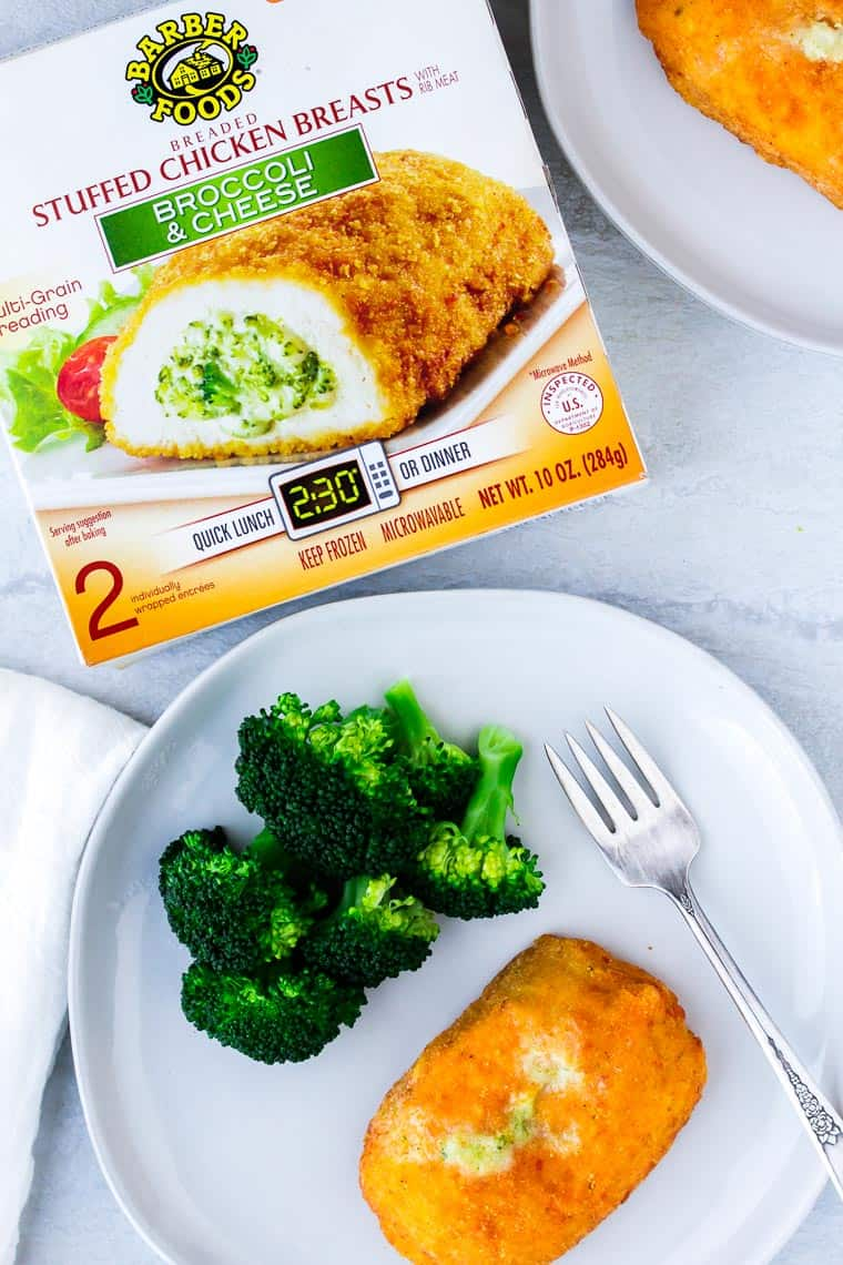 Overhead shot of Barber Foods Broccoli and Cheese Stuffed Chicken Breast box next to a white plate with a chicken breast and broccoli on it with a fork and white napkin