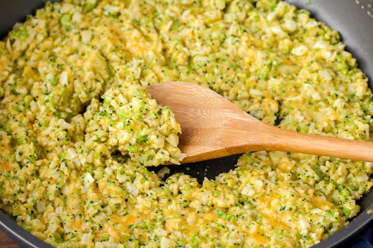 Cheddar Broccoli Cauliflower Rice in skillet with a wood spoon