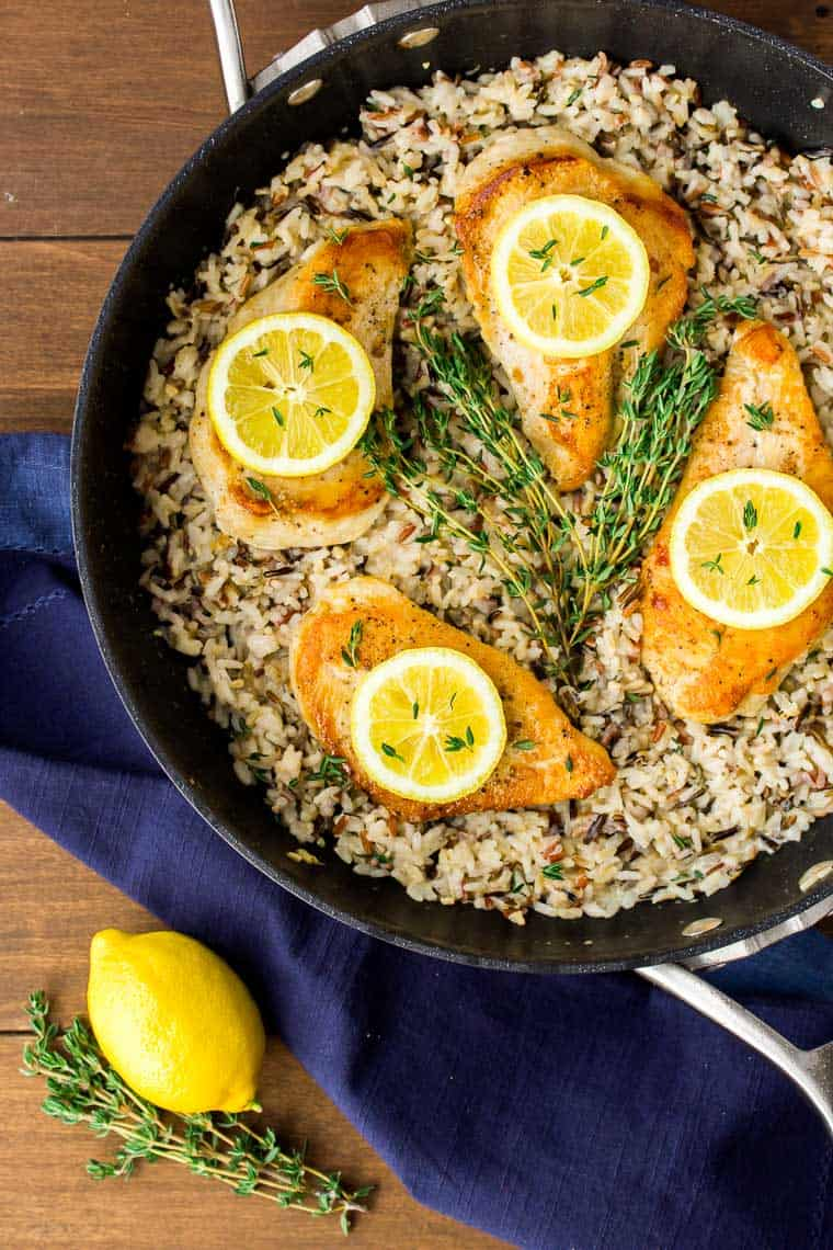 4 chicken breasts and rice topped with lemon slices and fresh thyme in a black skillet with a dark blue napkin around it and a lemon and more thyme next to it on a wood backdrop