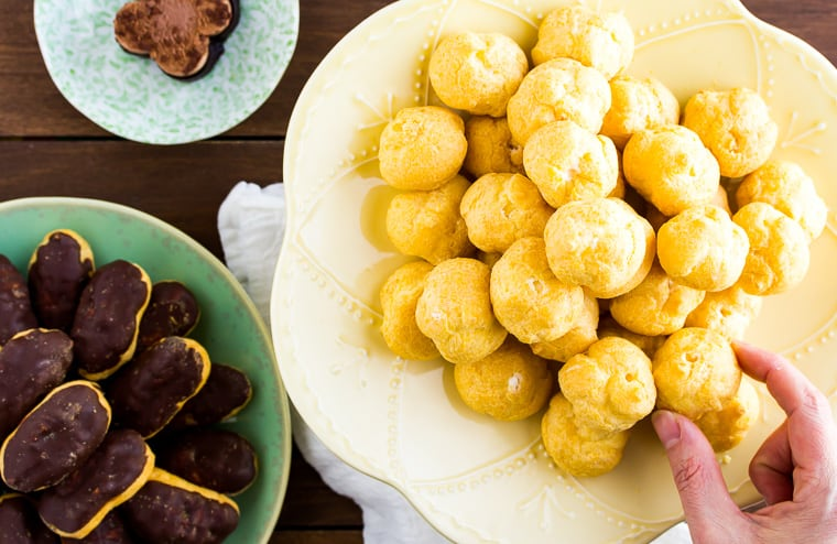 A hand placing a mini cream puff on a stack of cream puffs on a yellow cake stand with a green plate of eclairs next to it and a small dessert plate with a chocolate mousse on it all over a wood background
