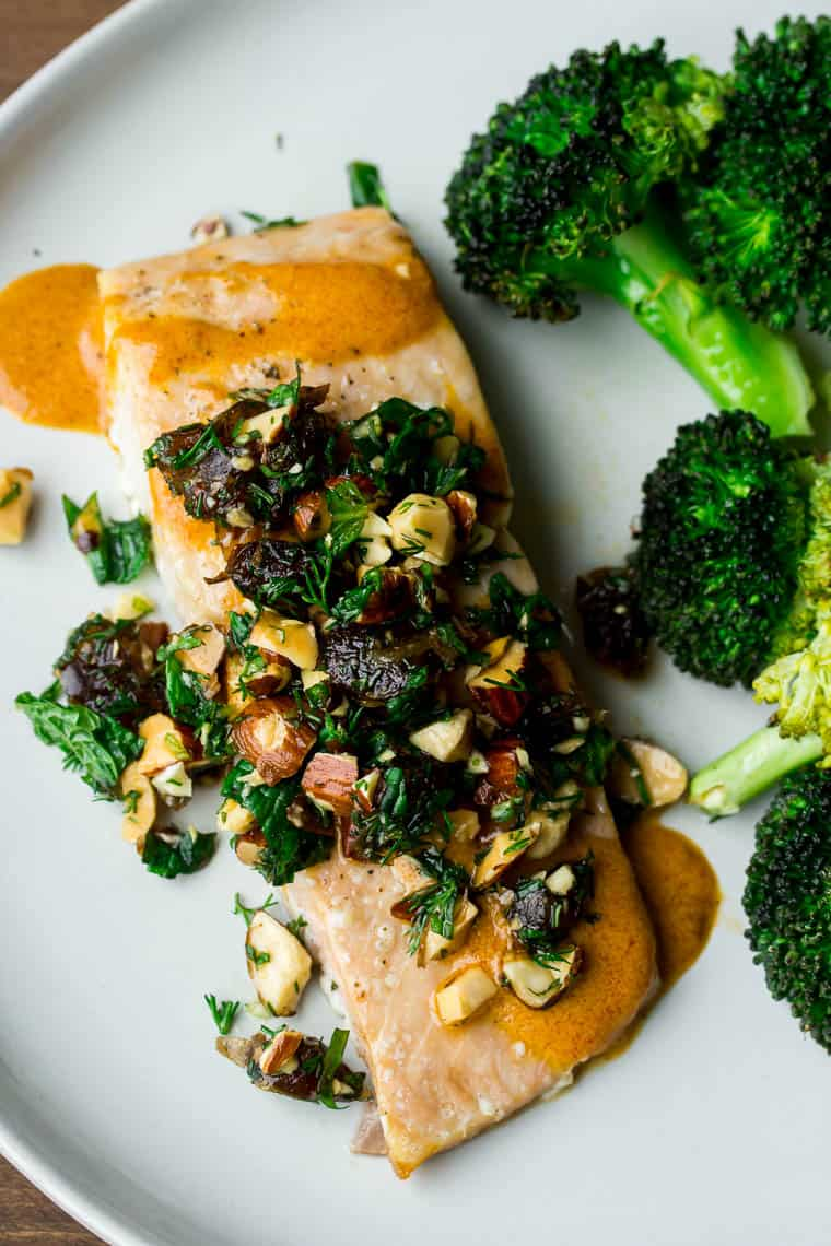 Roasted salmon topped with tapenade and a side of broccoli on a white plate over a wood backdrop