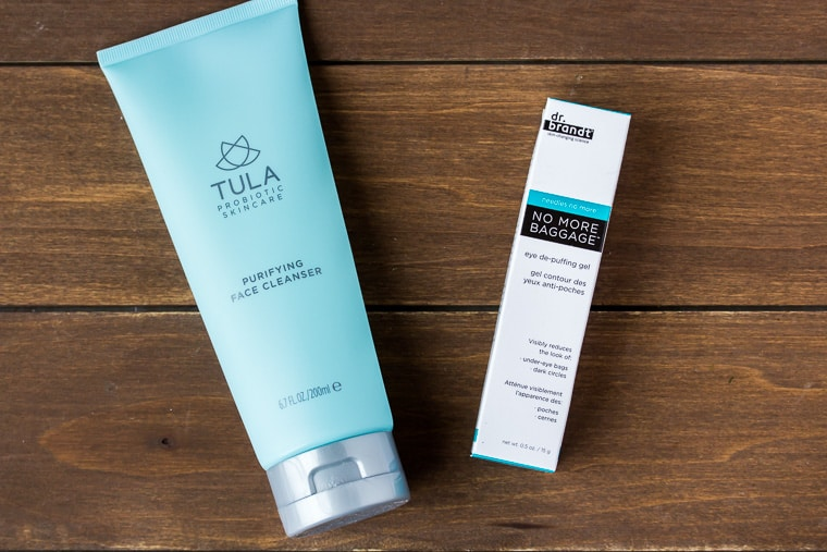 Tula Facial Cleaners and Dr. Brandt De-puffing eye gel on a wood backdrop