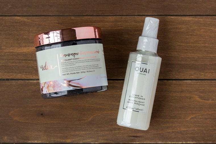 Ouai Leave In Conditioner and Manna Kadar body scrub on a wood backdrop