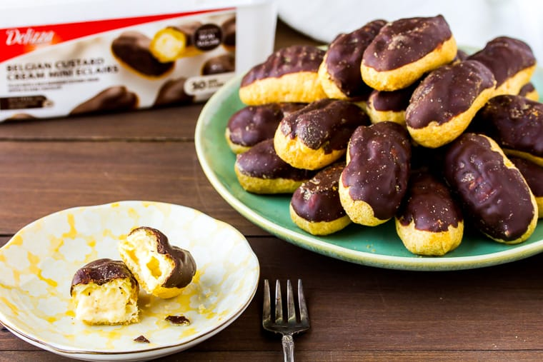 A gren serving plate full of mini chocolate eclairs with a smaller yellow plate with an eclair broken open and the box they came in in the background - all over a wood backdrop