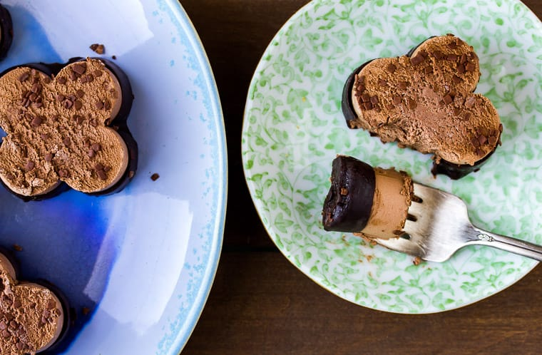 Mini Chocolate Mousse on a blue serving plate with one on a small green dessert plate with a forkful taken out sitting next to it