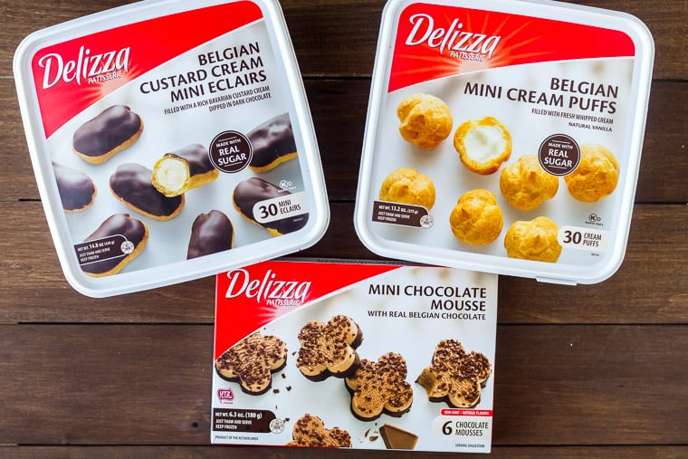 3 boxes of Delizza desserts including cream puffs, eclairs and mousse on a wood backdrop