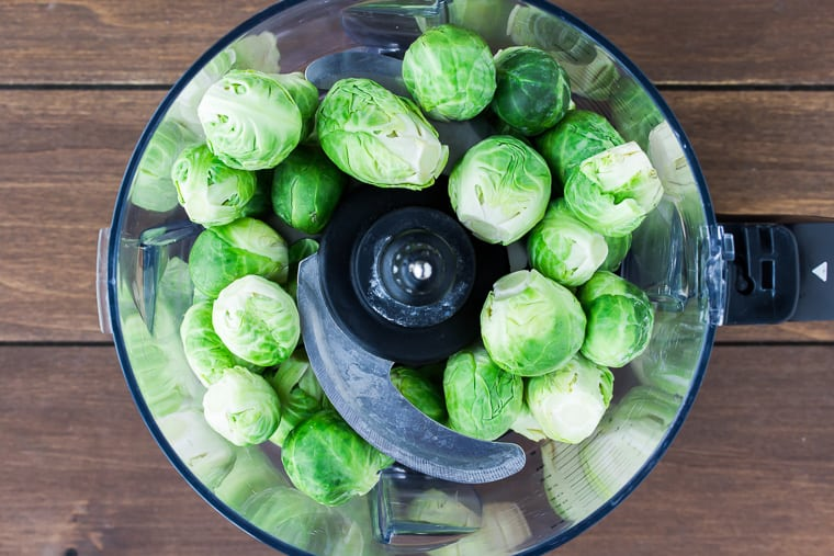 Brussels sprouts in a food processor over a wood background