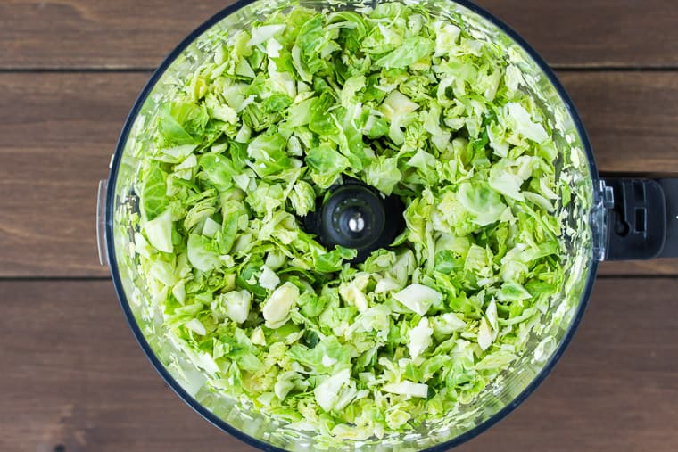 Brussels Sprouts shredded in a food processor over a wood background