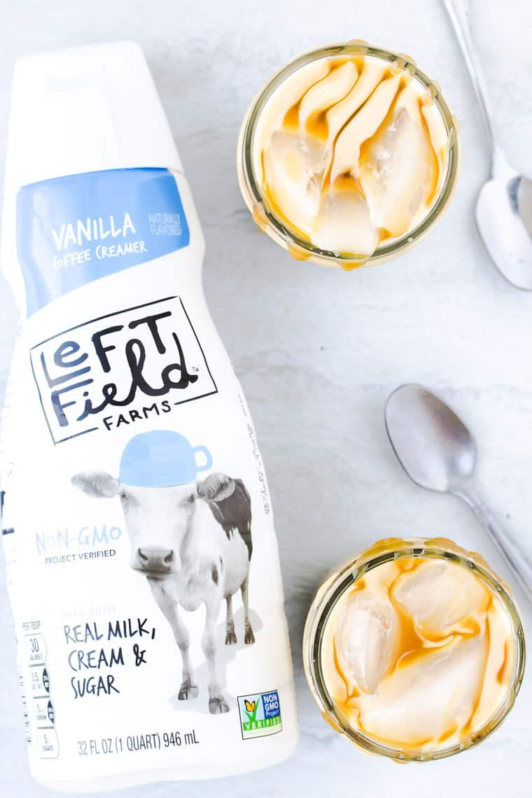 A bottle of Left Field Farms coffee creamer with 2 glassed of Iced Caramel Lattes and 2 spoons on a white background