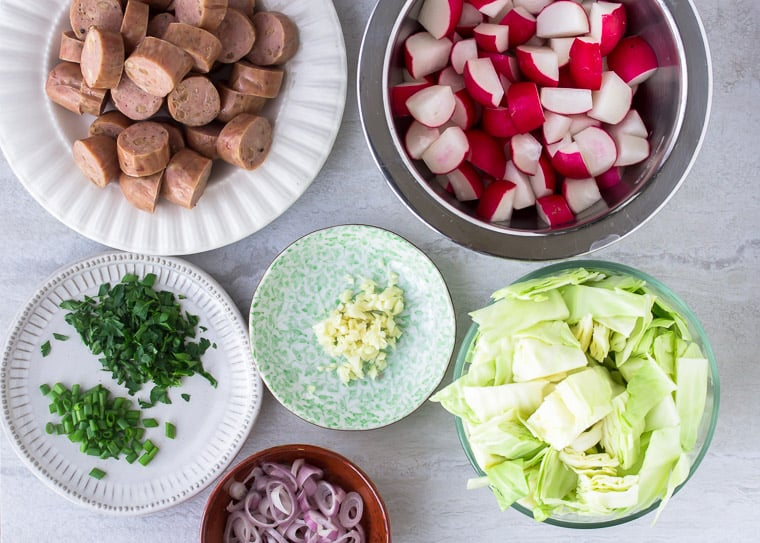 All of the prepped ingredients needed for the sausage, cabbage, and radish foil packets laid out in bowls and plates over a white backdrop