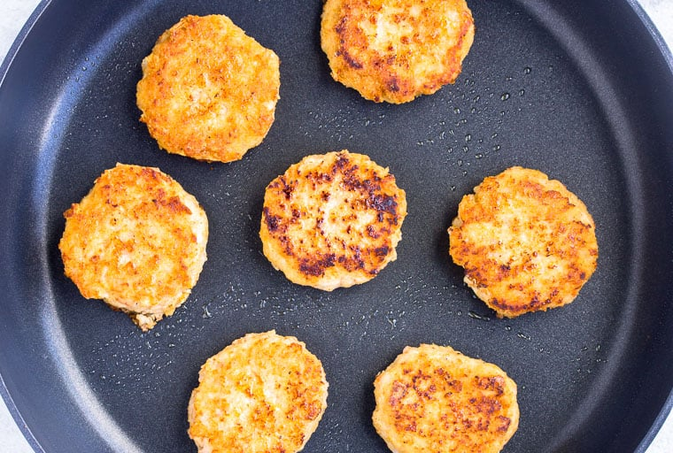 7 Shrimp Cakes frying in a large black skillet