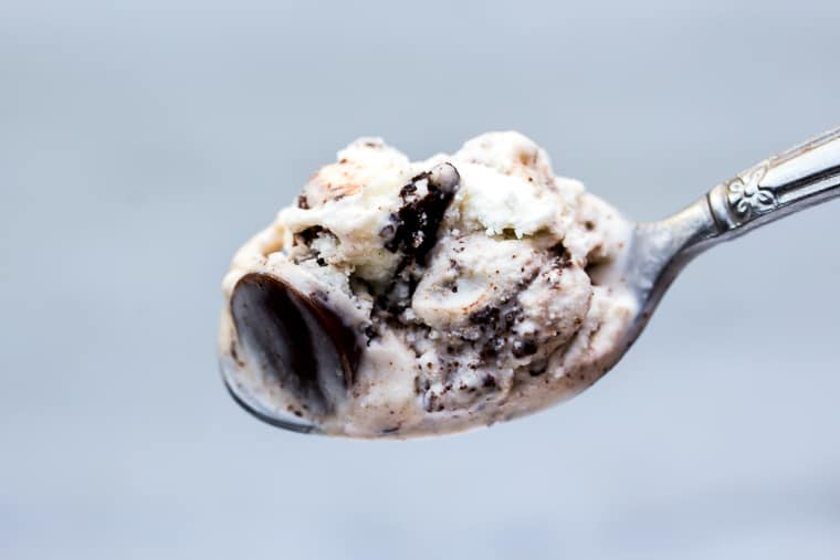 A close up of a spoonful of Moose Tracks ice cream that's vanilla with fudge and candy in it on a white background