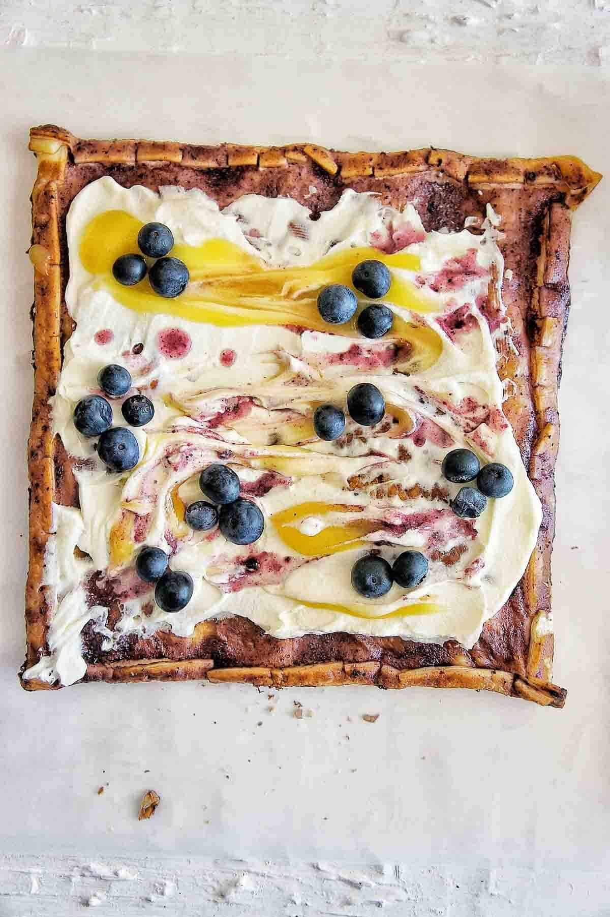 A puff pastry tart covered in blueberries, lemon curd, and cream on a white backdrop