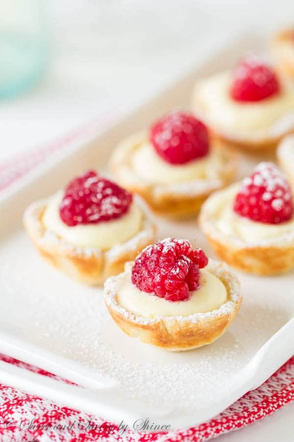 Mini Raspberry Tarts on a white serving tray with a red and white napkin under it