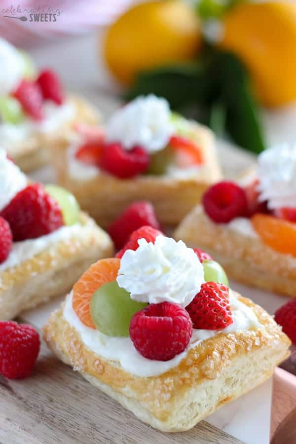 A white tray with mini cream cheese fruit tarts with lemons in the background
